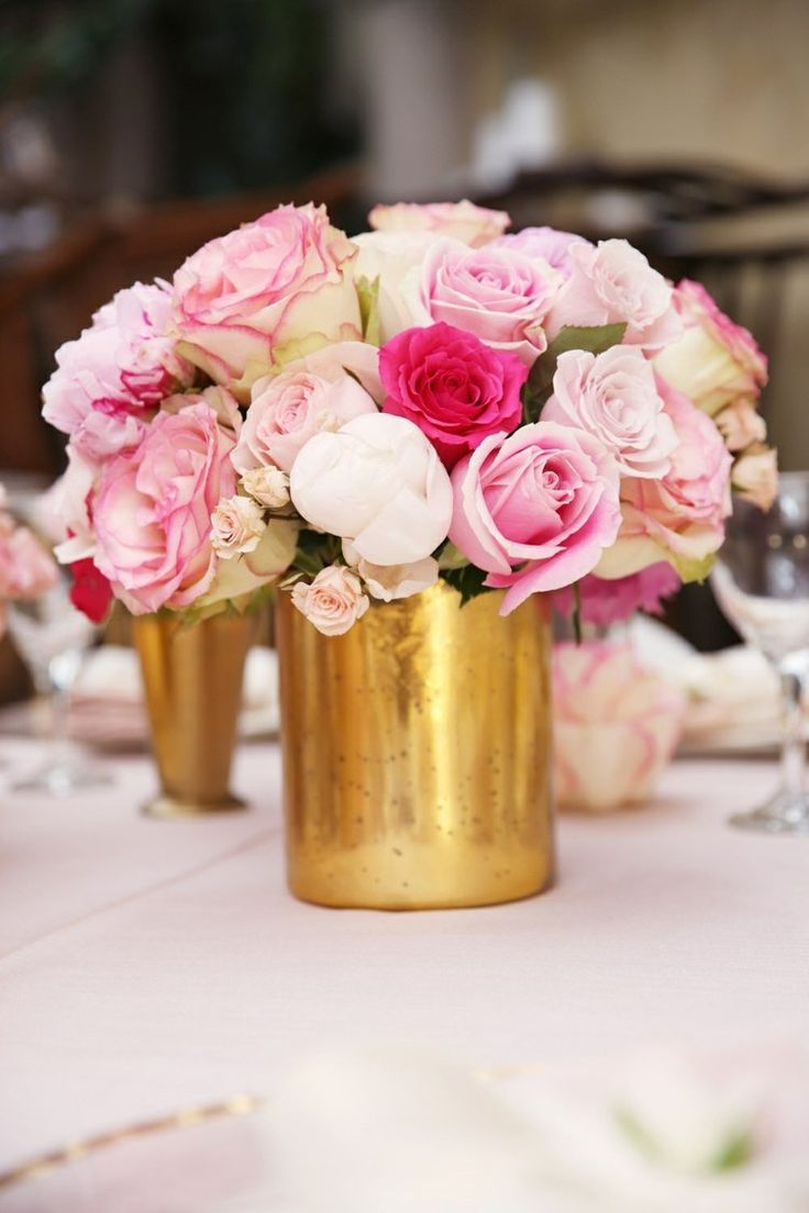 centre de table floral en roses délicates dans un vase de couleur or