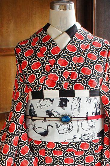 グラデーションのような綺麗な赤の縦ストライプに、白黒モノトーンのお花が連なるレトロモダンな格子モチーフが染め出されたウールの単着物です。