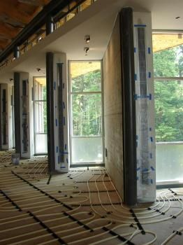 This construction photo shows the radiant floor slab installation and protection of the Trombe wall cavities.