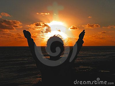 A child raising their hands to the setting sun praising God.