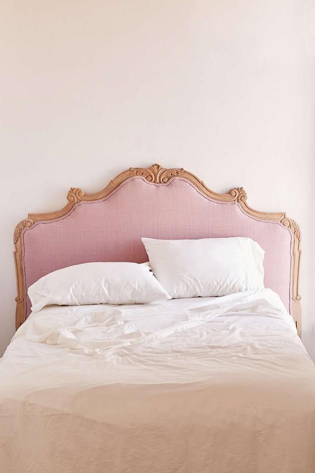 This curvy pink fabric and wood headboard!