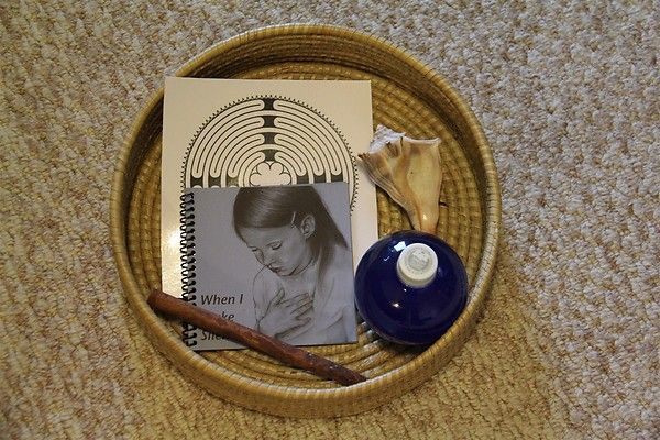 """Peace Basket for when somebody needs some quiet, alone time. Contains a whelk shell for the girls to hold up to their ears to hear the ocean (they have to be very still and quiet to hear the sounds of the """"waves""""), a finger labyrinth to trace, a cinnamon stick to smell, a book to read (When I Make Silence by Jennifer Howard), and our Starry Night Bottle to shake and then watch the """"stars"""" settle to the bottom."""