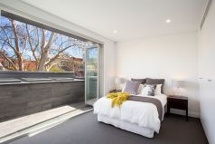 spacious bedroom, styled, private balcony, leafy aspect, manchester, bed side tables, lamps
