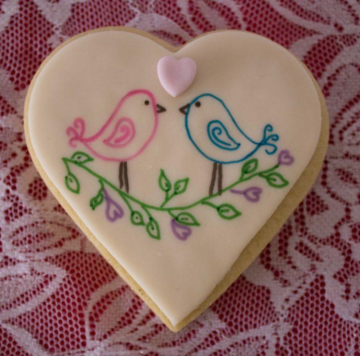 Hand-drawn love birds using edible pens on heart shaped vanilla sugar cookie with tiny fondant heart