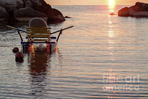 Pedalo moored in the sea at sunrise on a clear and colorful summer morning