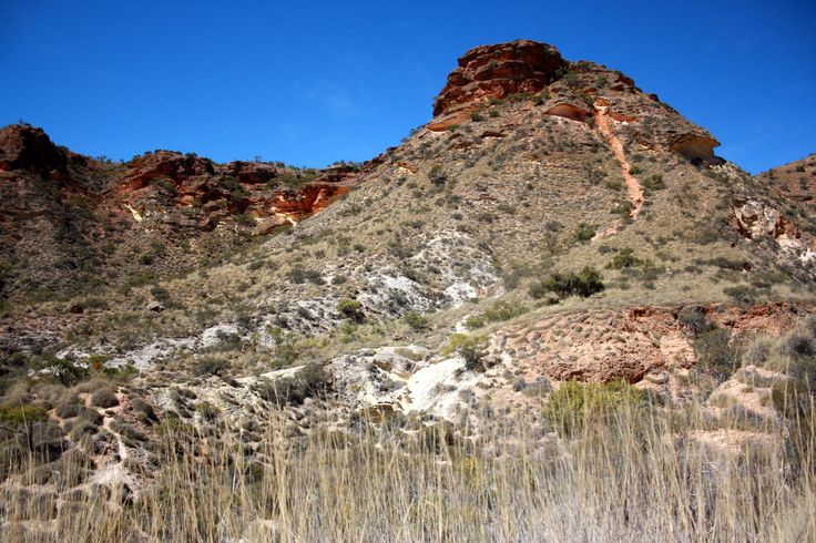 Boulder-scarred peaks covered with soft looking spinifex near the visitors' car park at Shot Hole Canyon, Exmouth.