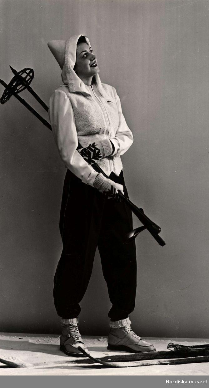 Vintermode 1939. En kvinnlig modell poserar iförd skiddräkt. Hon står brevid ett par skidor och håller ett par stavar i handen. Foto: Erik Holmén för Nordiska Kompaniet