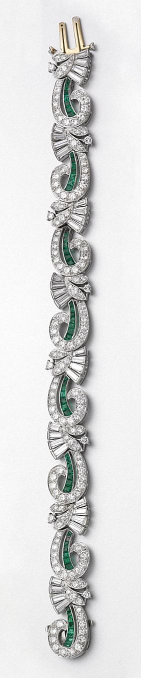 DIAMOND AND EMERALD BRACELET, TIFFANY & CO, CIRCA 1940. Designed as a continuous row of scrolls alternating with fan-shaped stylized floral sprays, set with 32 baguette and tapered baguette diamonds and 144 round diamonds weighing approximately 8.00 carats, further enhanced with calibré-cut emeralds, mounted in palladium, length 7 inches, signed Tiffany & Co.