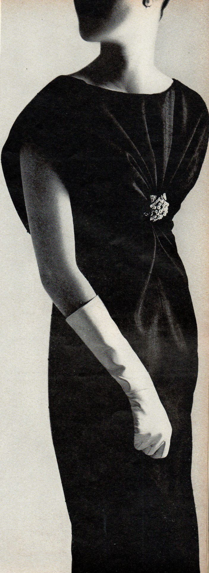 Givenchy black shantung dress, held by a jewel at the bosom drawn up over the shoulders  down on the back in two bias ends  crossed and sashed, gushed Vogue in April 1965. The dress was available at I. Magnin. Photo from Vogue.