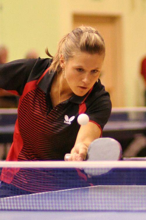 Atleta loira veste camisa vermelha e preta e, segurando uma pequena raquete…