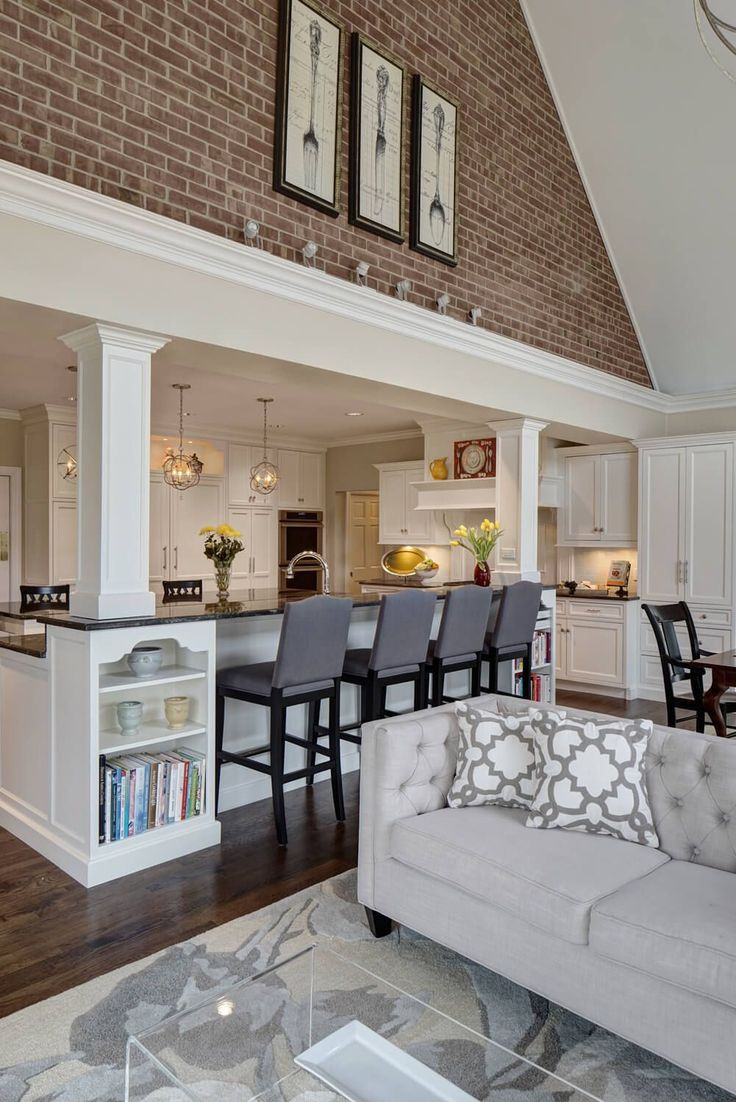 The kitchen expands into the open family room space, emerging beneath an immense vaulted ceiling with a red brick upper dividing wall. Rich dark hardwood flooring contrasts with light grey tones on the button tufted sofa, area rug, and bar stools. All-glass cubic coffee table sits in foreground, with built-in island shelving in white behind.