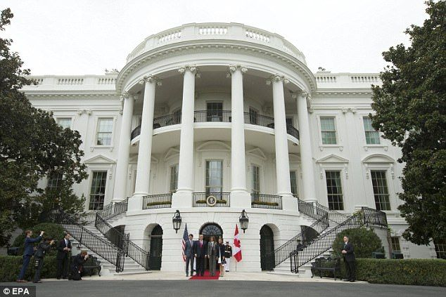 The two couples are seen posing for a photo this afternoon on the south side of the White House