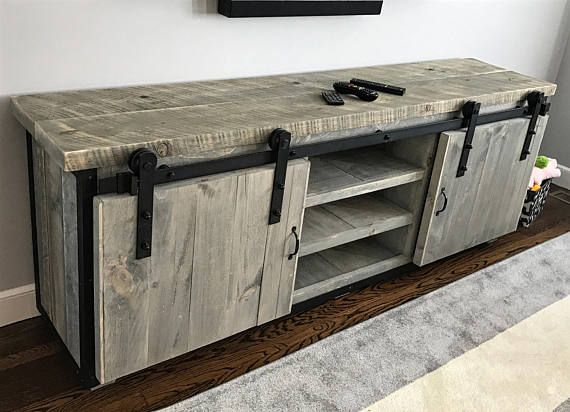This stunning reclaimed wood entertainment center has been crafted from genuine grey weathered rough sawn barn board, steel corners/trim and completed with sliding barn door hardware. It has been sealed inside and out with zero VOC water based lacquer. Equally at home in a rustic,