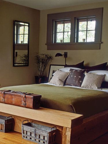 Photo by: Country Living Vintage Industrial For this master bedroom, a chunky cedar bed offers rough-around-the-edges appeal to a darker palette of olives greens and deep brown. For a masculine touch, an antique leather surveyor's case rests at the edge of the bed frame. Old zinc Popsicle molds reside neatly beneath a footboard-bench and may pressed into service as vases.