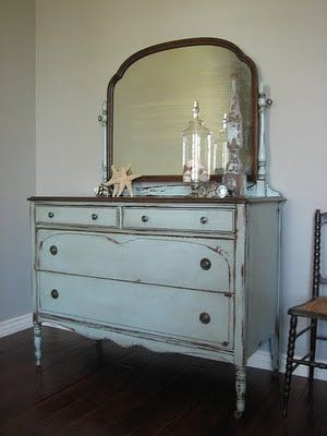 Blue Gray Mirrored Dresser. Antique mirrored dresser in a blueish gray, weathered chippy distressed finish with a heavy glaze. Love the brown stained top and mirror - makes this a gender neutral piece if you wished to put in a boys room or nursery. Stands on caster's. Four dovetailed drawers with original pewter hardware. By:europaintfinishes