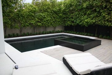 raised 4 side infinity edge spa. Complete re tile in black sheeted pebble and large format black granite on the spa. White concrete pool surround