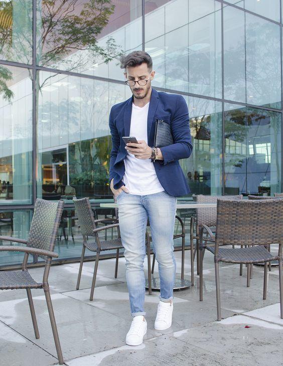 Acheter la tenue sur Lookastic: https://lookastic.fr/mode-homme/tenues/blazer-t-shirt-a-col-rond-jean/20041 — Blazer bleu marine — Pochette en cuir noire — T-shirt à col rond blanc — Jean bleu clair — Baskets basses en cuir blanches