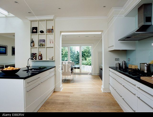Wooden flooring in large modern kitchen with doorway to dining room and black granite worktops on white units Stock Photo