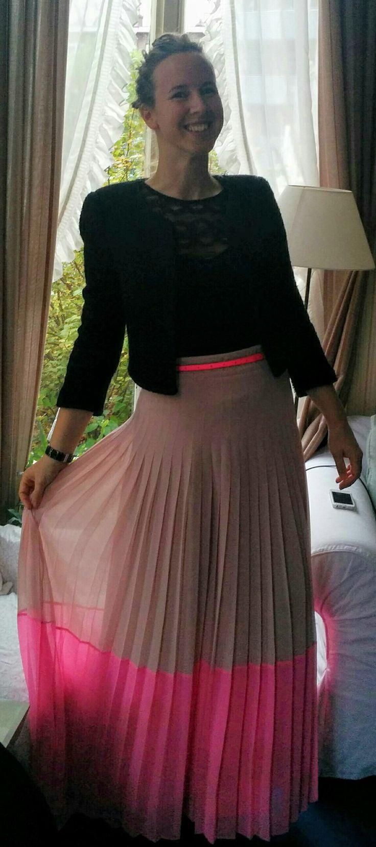 Jeanne in vette lange plissé rok met neon roze accent. Niet alleen geschikt voor feestjes