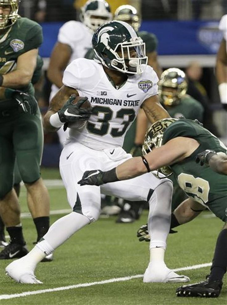 Michigan State running back Jeremy Langford (33) breaks a tackle against Baylor safety Collin Brence (38) on his way to score a touchdown during the first half of the Cotton Bowl NCAA college football game, Thursday, Jan. 1, 2015, in Arlington, Texas. (AP Photo/LM Otero)