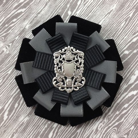 this rosette features a silvertone filigree, surrounded by tiers of velvet and grosgrain ribbons in shades of black and grey. this rosette measures approximately 4.75 inches wide and 4.75 inches tall. all mossbadger rosettes have a combination back so they can be worn as a brooch or hairclip.