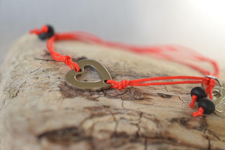 ČERVENÝ-Vyrobený z červené hedvábné šňůrky, dvojitě svázané, posuvné zapínání pomocí uzlu, s komponentem srdce z chirurgické oceli velikosti 1 cm. Dozdoben  černými matnými korálky a medailonkem Impronte.  Podle Kabbala tradice je  červená barva symbolem ochrany před negativní energií a nemocemi. Nejvhodnější je nosit náramek na levém zápěstí, protože levá strana je příjemcem energie.  Na Vaše přání rády nabídneme do setu náramek z drahých kamenů hodící se k tomuto náramku.