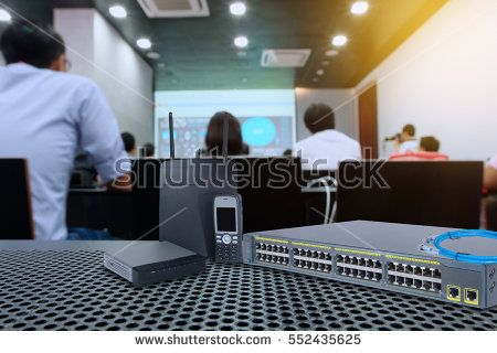 Network switch gigabit port utp and sfp and wireless access point for high speed network on Table mesh in training or conference room and blur background.