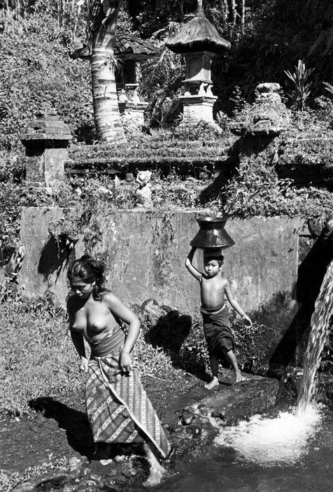 Henri Cartier-Bresson - Bali. 1949. Near a village, a child carries cooking water. In the background is a temple dedicated to the gods of the forest.