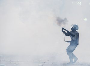 Riot policeman fires teargas at opposition activists