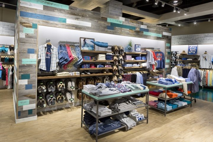 The interior store layout is a metaphor for the breaking waves that inspired the angled layout of the fixtures. Fixtures are clustered in stories - much like campfires around which customers gather along the shoreline. A signature deep aqua resin concrete flooring defines the area for the sandbar and customer service.