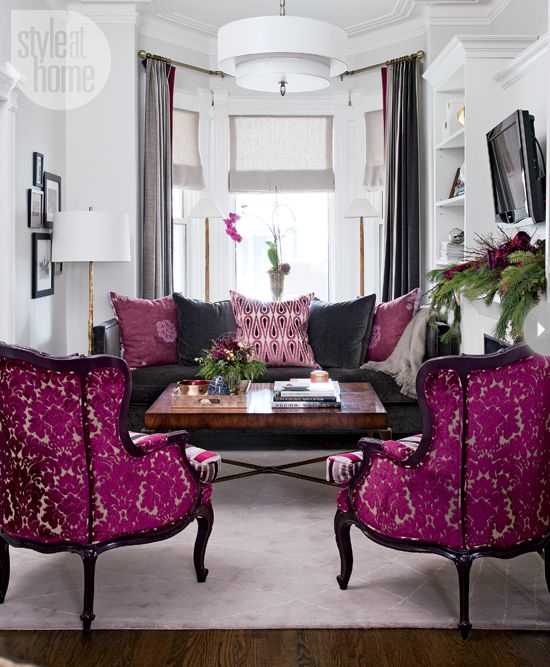 Luxurious velvet in deep charcoal serves as the backdrop for the sofa's vibrant magenta and pink throw pillows. Across the living room, cut velvet damask and stripes enliven two armchairs that both celebrate and wink at tradition. Warm white walls and large-scale modern light fixtures soften the happy palette.
