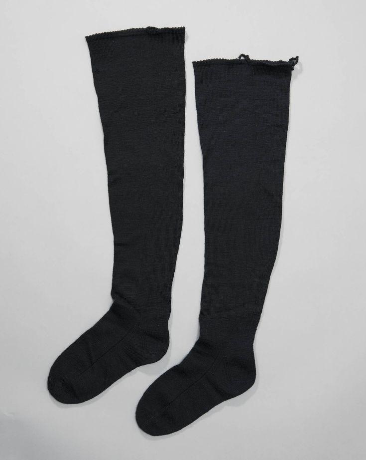 zwarte kousen, vrouw, Katwijk Gebreide zwarte wollen kousen, aan de bovenkant afgewerkt met een gehaakte rand. Daaraan 2 gehaakte lusjes om de kous op te houden. Deze kousen lijken dus gedragen te zijn met jarretels. voor 1953 #ZuidHolland #Katwijk