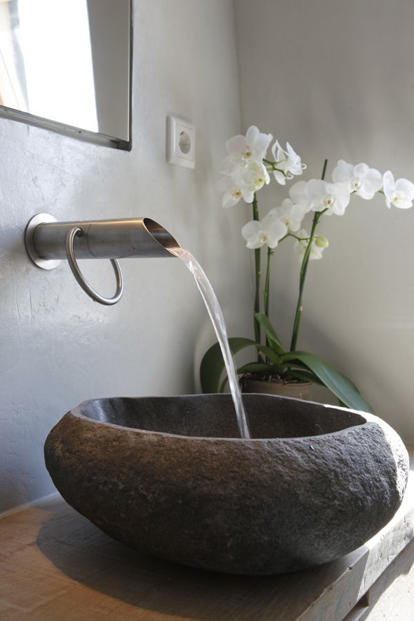 The water flows into free standing stone made sink like spring water.