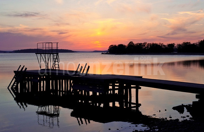 Sunset with the silhouette of a jetty and diving tower in the foreground  © Arno Enzerink / www.stockphotography.nu All rights reserved.