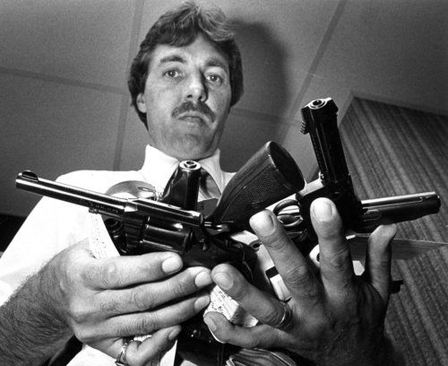 """Morton Grove, May 19, 1982: Morton Grove Police Officer Robert J. Jones, administrative assistant to the police chief, holds handguns turned in by the town's residents after the village banned their possession on Feb. 1, 1982. """"They are the most photographed guns in the world,"""" he said, speaking of the world-wide interest in the Morton Grove law."""