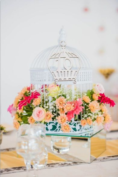Monte Vista Venue pink and gold centerpiece with flowers in a white birdcage, a pink laser cut birdcage table number hanging from the birdcage, all on a mirror box with 4 gold floating candles in glass bowls around it.