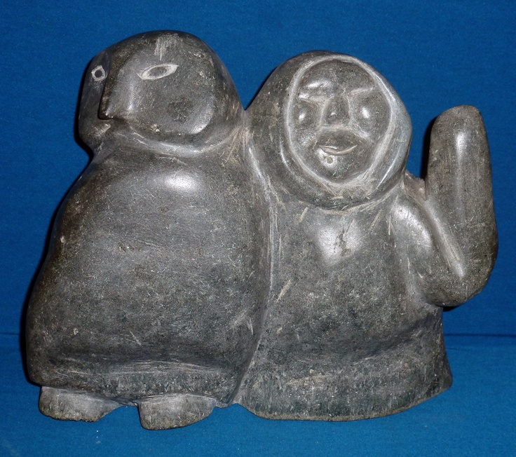 """Item # S5001 Price: C$3,200 Subject: Link   Owl & Inuk Dated: c.1970's - Signed Artist: Link   Unidentified      Community:  Unknown       Size: inches/cm 11.5"""" x 13.5"""" x 5.5"""" 29.2 cm x 34.3 cm x 14 cm   Description: This is an interesting and curious carving. The pale grey basalt has been roughly worked into revealing our """"odd couple"""", then polished to a fine sheen, especially on their bellies."""