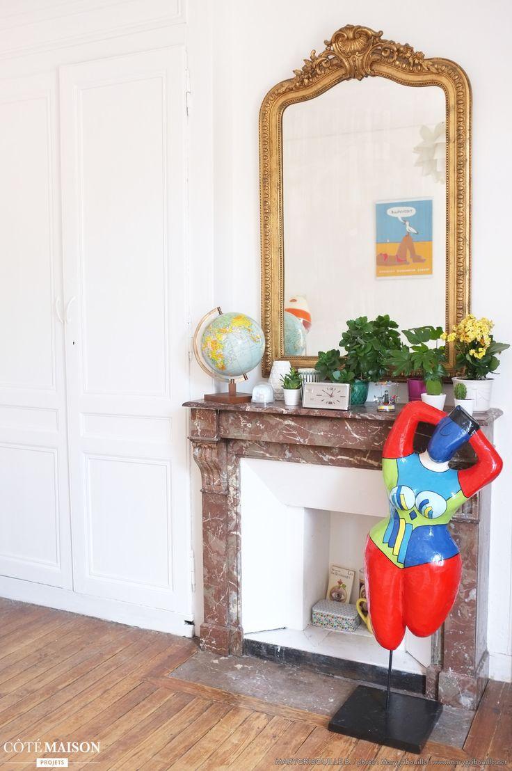 Typique de l'appartement haussmannien, la cheminée en marbre et le miroir doré font la part belle à l'authentique
