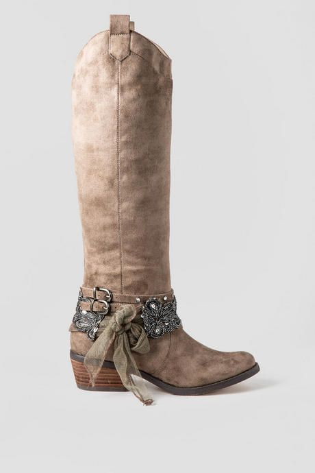 Rhinestones, chains and studs, oh my! The Midnight Dream Embellished Boot features a faux suede upper ornamented with double buckles adorned with rhinestones and a shining floral embellishment, all finished with a precious softnet bow. To add some rustic flair to a casual cool look, throw the Midnight Dream Embellished boot in with a sweater dress