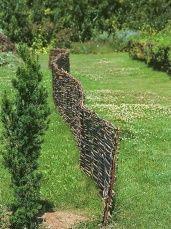 Zvlněnou proutěnou stěnu podporuje živý plot, který časem převezme její funkci