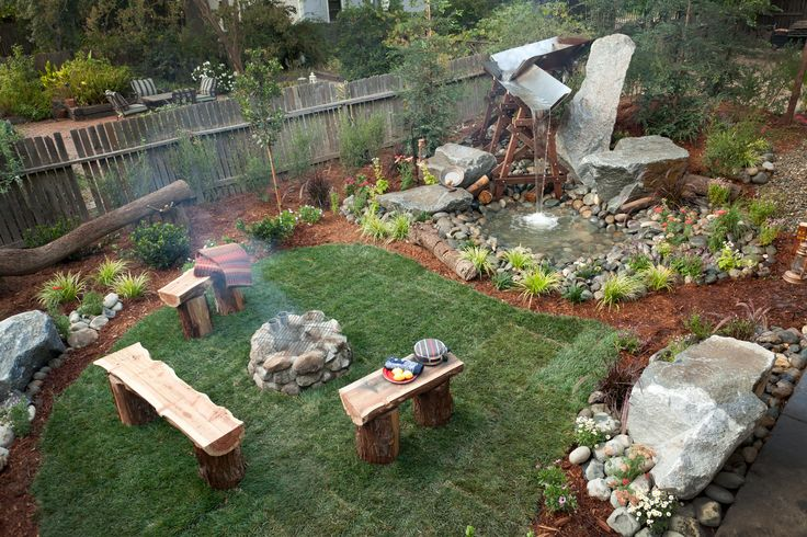 Rustic mountain backyard design. Inspired by the Sierra Nevada's, complete with redwood stump benches, stone fire pit and grilling area and log flume water feature. Photo by Mike Graff