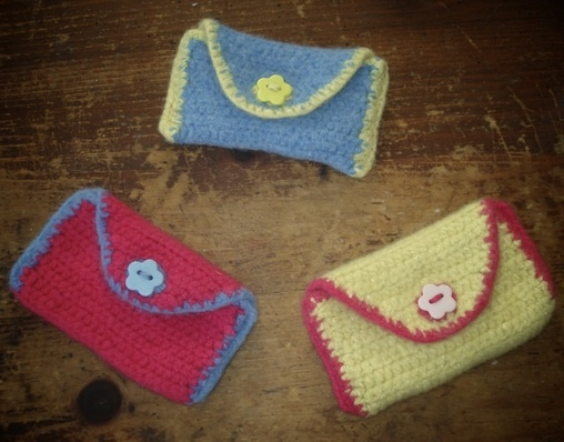 Gorgeous little purses - just the thing for carrying a packet of tissues, your lipstick, whatever!    Pink with blue trim, blue with yellow, and yellow with pink, each topped with a button in the same colour as the trim (other colours are available - try me!)!    Crocheted using 75% lambswool and 25% silk (pink is lambswool and cashmere), then felted to give them strength and texture, these purses are **sooo** sweet and soft! Lovely!    £5 for one (£8 for 2, £12 for 3) + p&p.