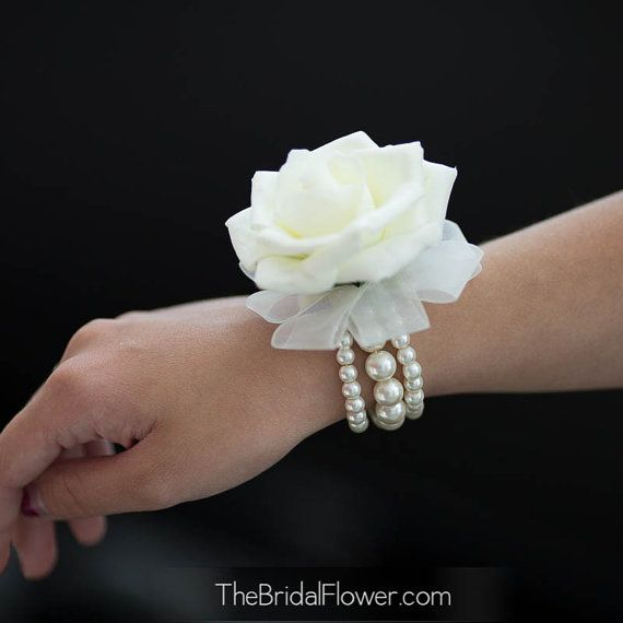 Simple but stunningly elegant wrist corsage with one cream rose (soft-touch, velvety feel), set on a pearl bracelet. Accented with ivory sheer ribbon. Pearl bracelet will match the rose color (white or cream). Great for wedding or prom! About 2.5in diameter of the rose  Thank you so much!!  ~ Irena @The Bridal Flower