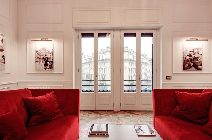 A classy chic apartment in central Milan by Nomade Architettura http://www.nomadearchitettura.com/#all  red velvet custom made sofas, timber floor, black and white pictures, photos