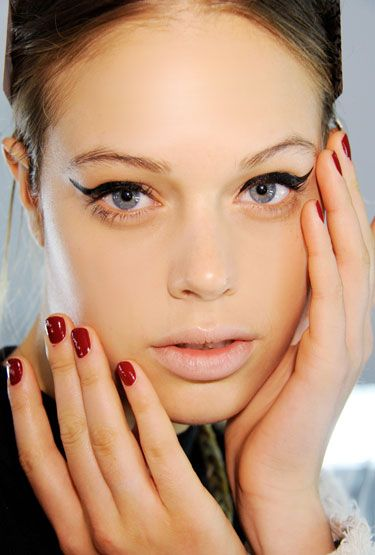 Winged eyeliner and bold red nails - so ladylike.