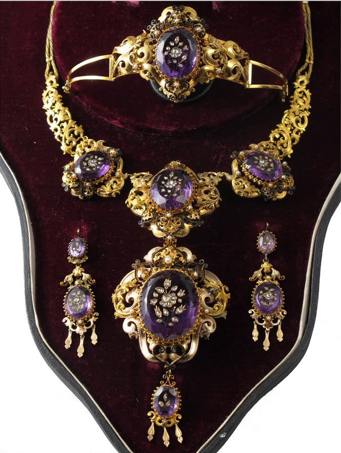 A yellow gold and amethyst parure composed of necklace, pendant, earrings and a bracelet. Diamond inlay on amethysts. England, around 1850.
