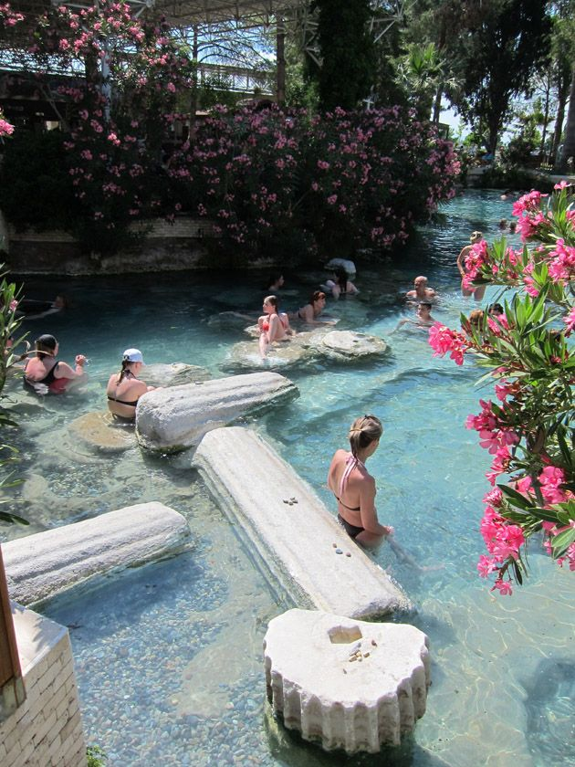 Swimming in Apollo's Pool with ancient ruins in the Hierapolis hot spring, Pamukkale