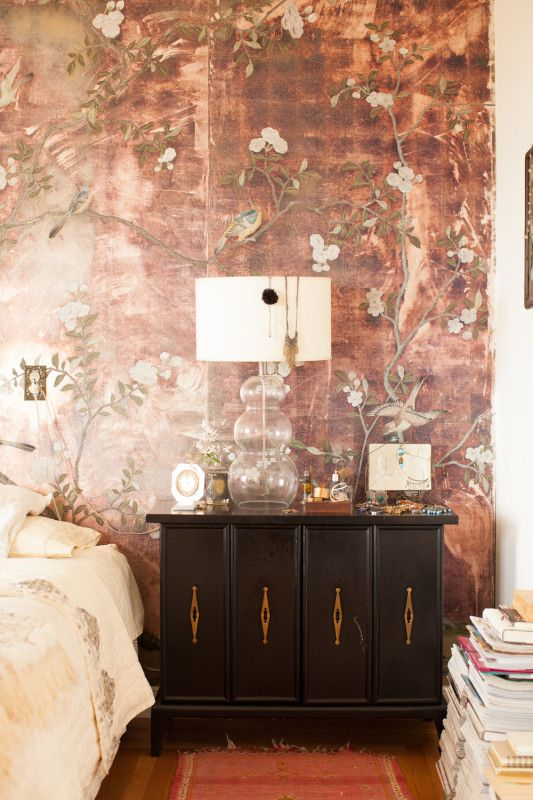 Bohemian elegance floral wallpaper combined with a dark chest plenty of books and a lamp that doubles as a jewelry hanger