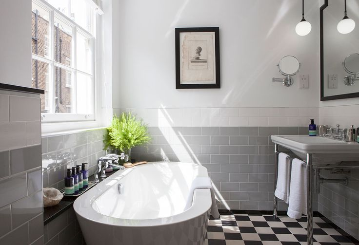 This stylish family bathroom is light and airy with monochrome flooring and a stunning freestanding bath.