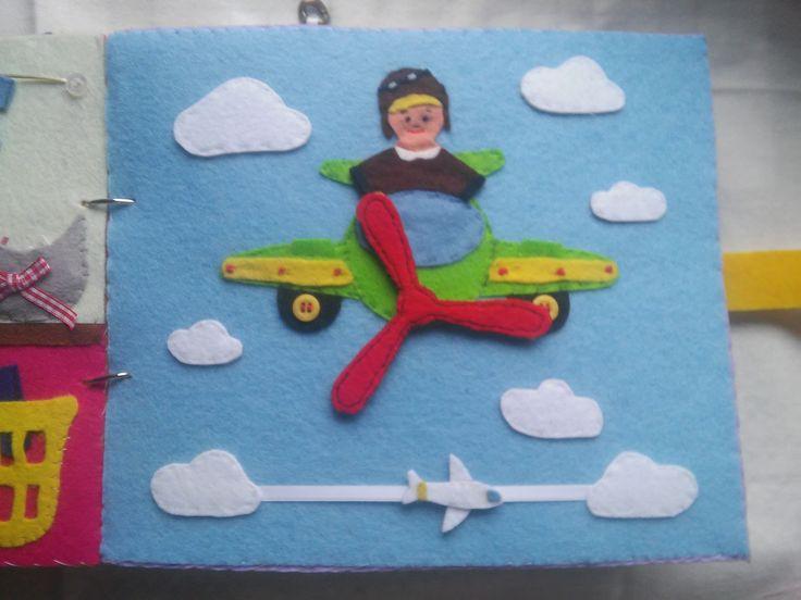 """Quiet Book - Livro Interactivo, pág 4 """"O Aviador"""", em feltro, botões e fita, a hélice do avião roda e é amovível. O avião pequeno desliza pela fita!"""
